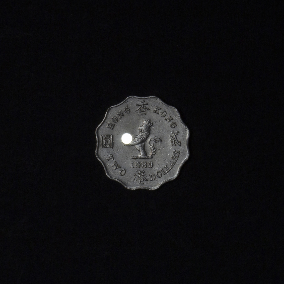 A coin carving with a lion holding on a pearl of the orient. We drilled a hole on the pearl and turned it into pinhole lens.