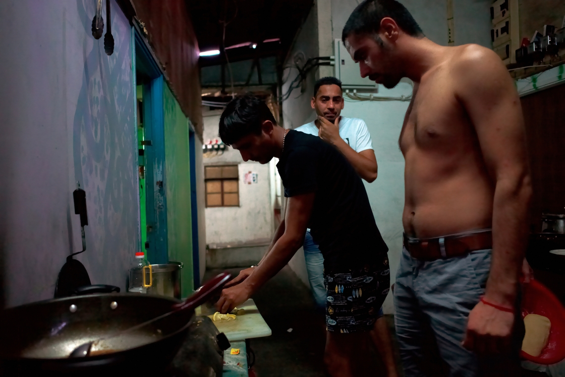 Three young refugees from India are preparing dinner in a slum in Nai Wai. A real solidarity exists between the refugees. Hong Kong, August 2015.