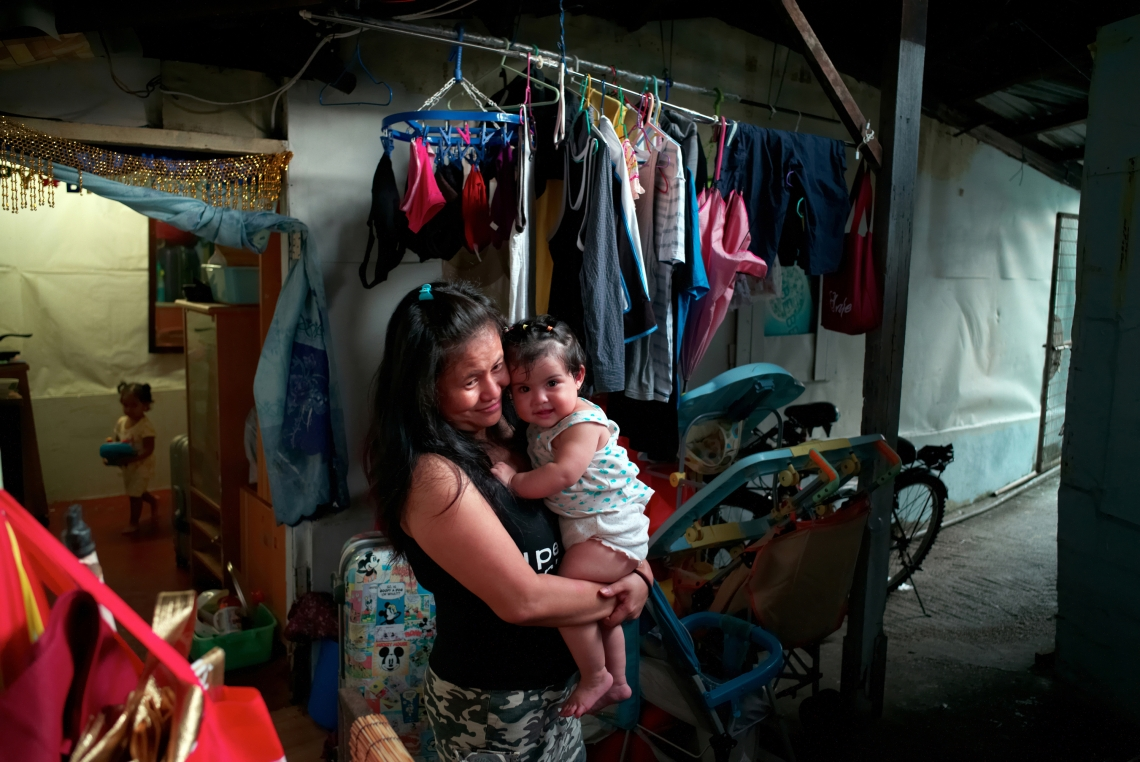 Suneisha, a 30 year old Indonesian carries her neighbor's daughter in a slum in Lam Tei. The subsistence assistance provided by the social services is particulary insufficient for families with children. Hong Kong, July 2015.