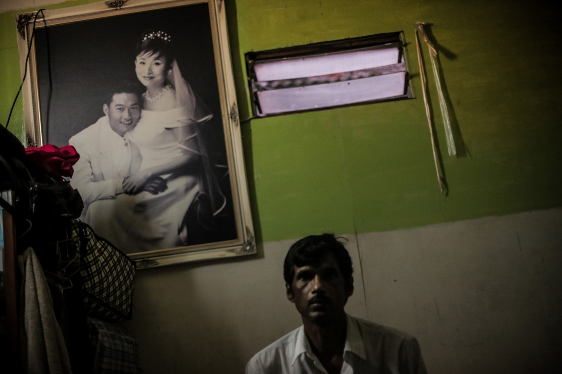 Ali, 38, asylum seeker from Pakistan, sitting in his small room in Hong Kong. In order to add some liveliness to his empty home, he hung a wedding photo on the wall as a new decoration. The photo was picked from a garbage heap.