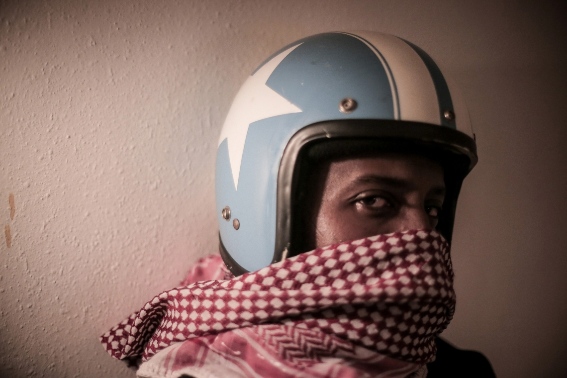 A Somali refugee, Adam, 28, posed for a photograph with a helmet he bought from a second-hand market. The white star and light blue background coincides with the flag of his country, while his red scarf was brought along with him from his hometown. To relieve the homesickness, he hangs the helmet on the wall and wraps the red scarf around it, and symbolizing the civil war in his country.