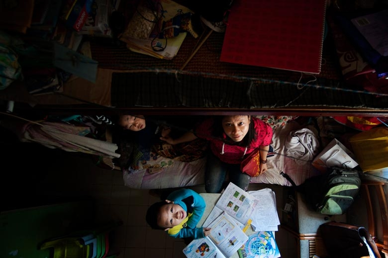 A couple and their two sons live in a 200 sq. ft. rooftop house in Sham Shui Po. In summer, the room temperature is over 30℃. Because the flat has no air-conditioning, the mother takes her children to the library to cool themselves, 2011.  From the series 'Cents' Mansion.