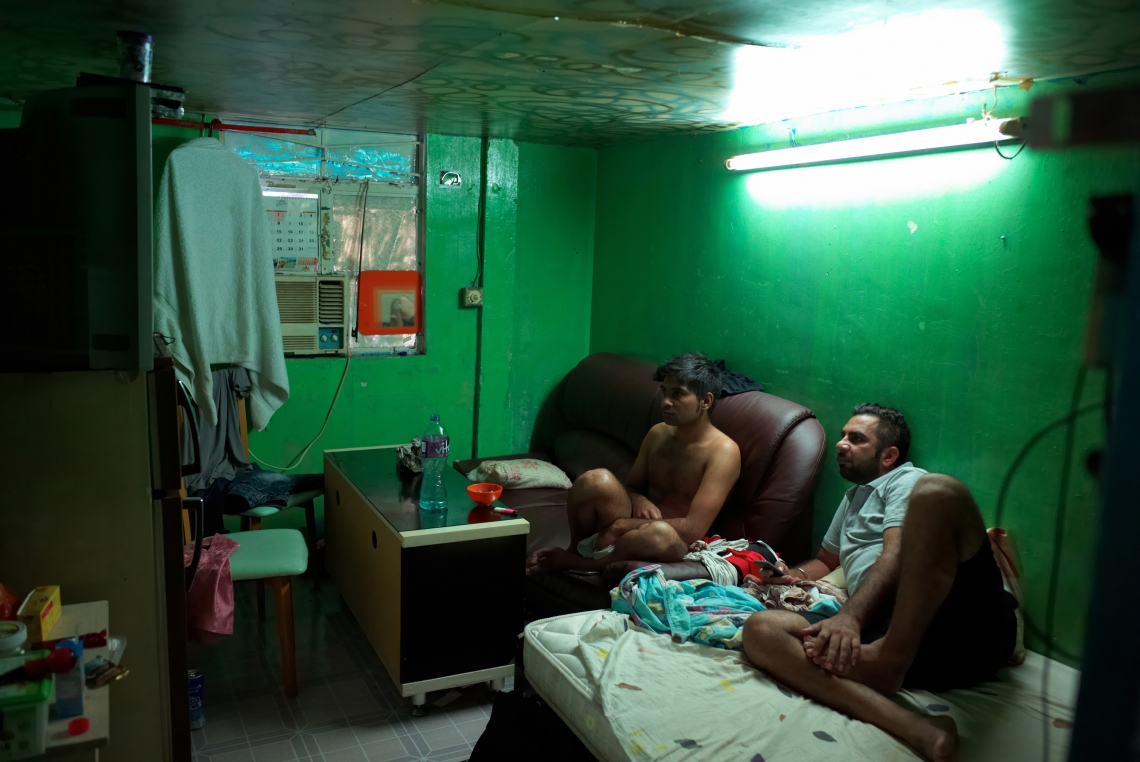 Two Indian refugees are watching television in the room they share in a slum in Nai Wai. This slum is a former pig farm transformed into housing. Hong Kong, August 2015.