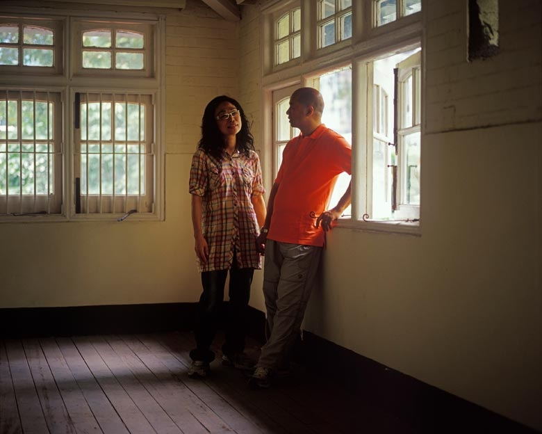 Mr. and Mrs. Chan stand in what used to be their kitchen when they lived in these employee quarters of the Government Supplies Department on Oil Street, North Point in the 1990s. Mr Chan was a driver for the Department.
