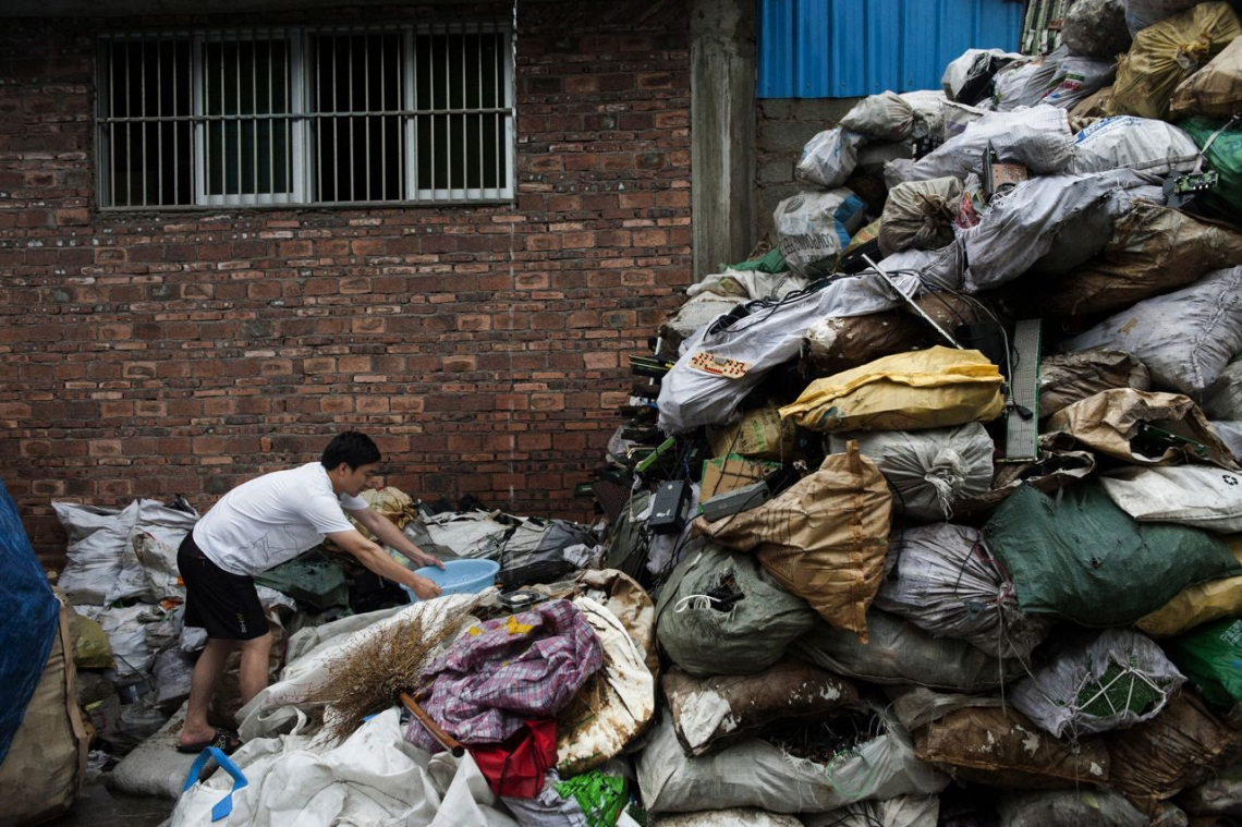 A Guiyuzhen City neighbour collects rain water for cooking, forced to climb amongst mountains of electronic waste bags. After ten years of recycling work, the water supply of this small town has become the most contaminated in China. Guiyu, China. May 2013.