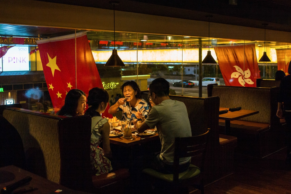 The day before the 20th anniversary of the reunification, people were having dinner in a restaurant. Outside, the Chinese national flag and the HKSAR flag were flying in the wind.