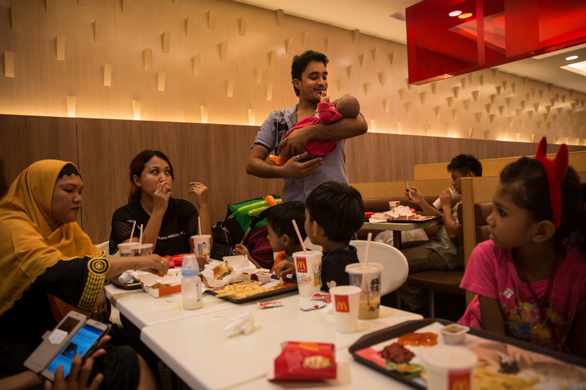 Arif, centre, holds his new born baby as his family have a meal in a Hong Kong Mcdonalds. Arif is a pharmacology student, who fled his native country in 2009 when terrorists threatened to kill him, and came to Hong Kong waiting to receive state support as refugees for 7 years. He had a baby in 2015 and married an Indonesian woman in 2016, they established new lives in a transitory locale.