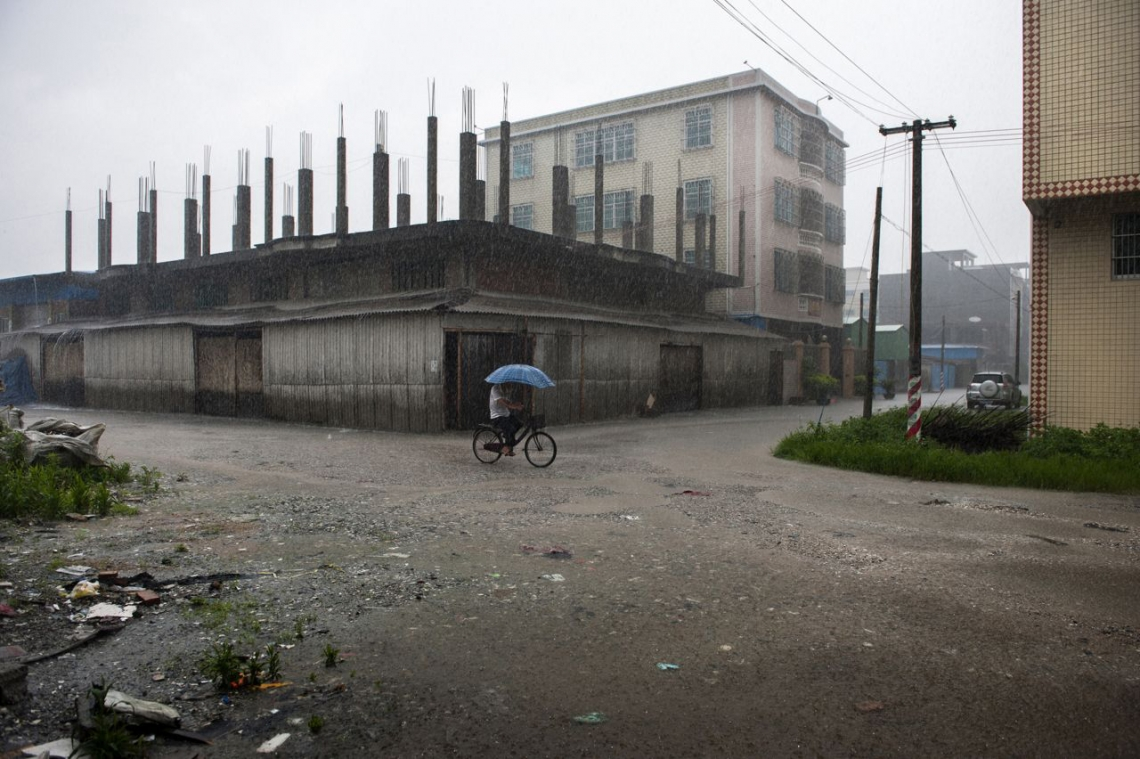 A man riding his bike in the rain in polluted Guiyu, China. May 2013.