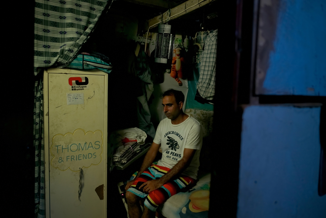 Paula, a 37 year old refugee from Pakistan, in Hong Kong for 7 years, sitting on his bed in his tiny room without windows nor air conditioning in a slum in Lam Tei. Hong Kong, July 2015.