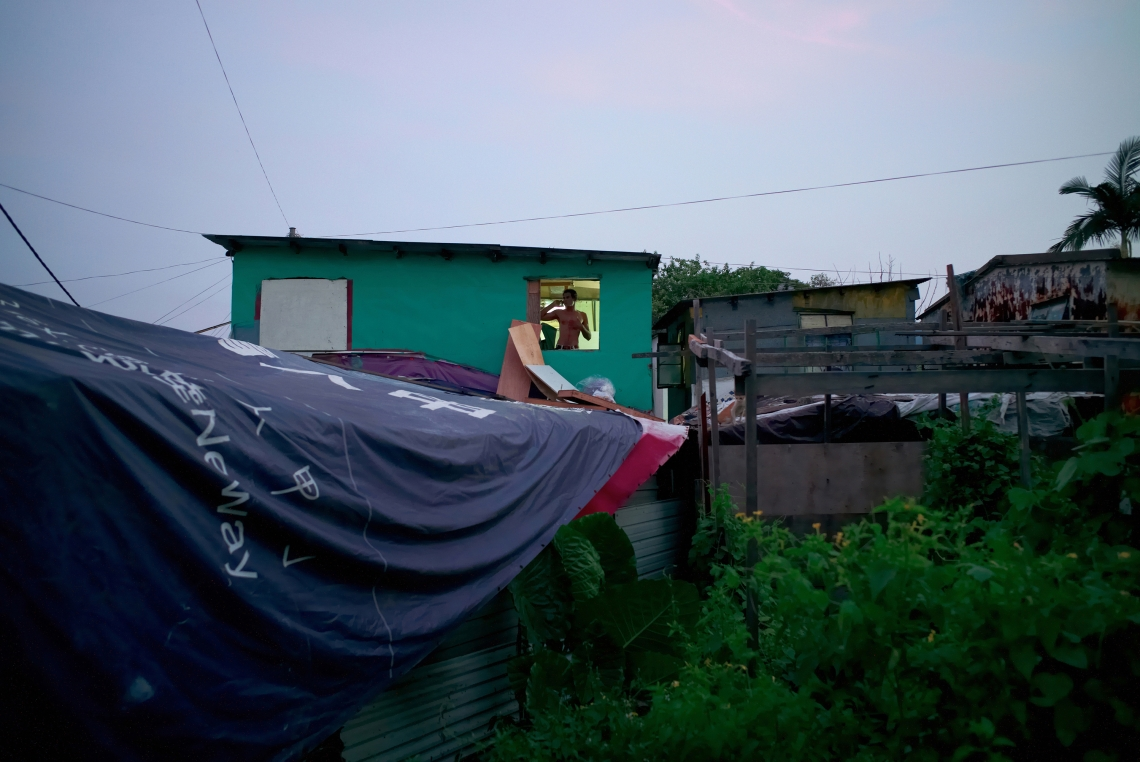 Ramesh, a 35 year old Sri Lankan, in Hong Kong for 8 years, is on the phone at the window of his shack that he built by himself in a slum in Lam Tei. About forty people live in this slum. Hong Kong, July 2015.
