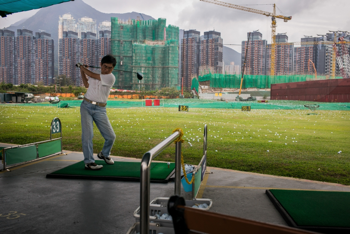 "A man golfing in front of residential buildings and construction sites. The identity crisis of Hong Kong people gradually surfaced after the reunification. Family members of previous generations are often directly, or indirectly related to the Great Escape. The identity of ""old immigrants"" that took root here conflicts with that of ""new"" Hongkongers."