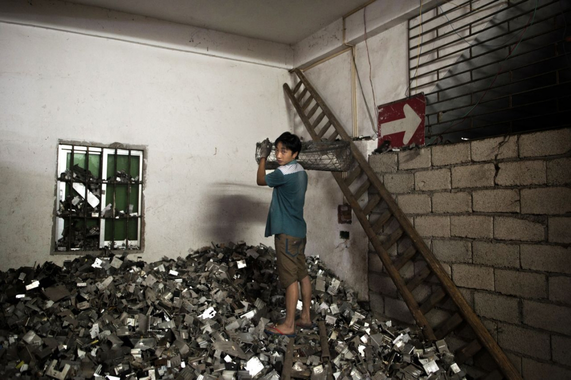 A boy loads electronic remains into a cart inside an illegal garage. Guiyu, China. May 2013.